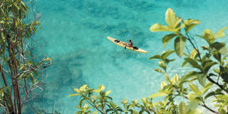 a kayak floating in the turquoise blue sea