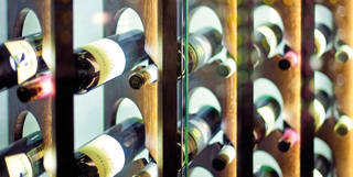 Rows of wine bottles behind a contemporary glass wine case