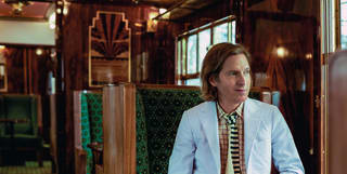 wes anderson seated on the british pullman train