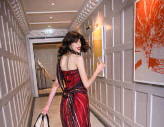 Donna in abito elegante sorride tenendo in mano un bicchiere di champagne