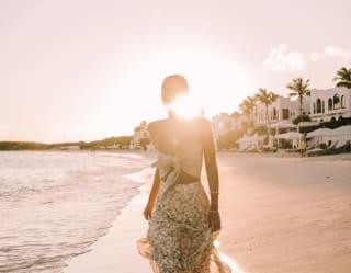 Mulher passeando em uma praia de areia ao pôr do sol
