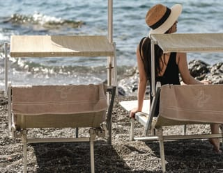 A lady wearing a straw hat sitting on a beach chair looking at the sea