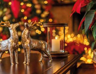 dettaglio di due decori a forma di renne dorate di fronte a un albero di natale