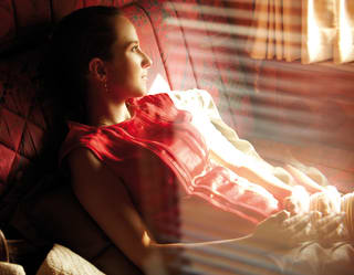 Lady reclining on a day bed in a luxury train cabin