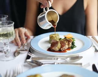 a steward is pouring a gravy over a guest's dish
