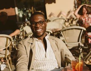 Uomo sorridente con una camicia a righe seduto a un tavolino all'aperto