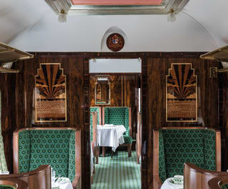 Aisle of a Pullman carriage with marquetry and armchairs designed by Wes Anderson