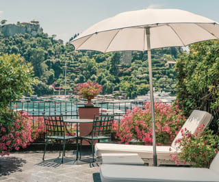 A parasol and sun loungers on the balcony of Splendido Mare balcony over looking the Portofino harbour