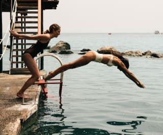 two women diving in to the sea