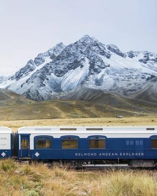 Vagões azul-marinho e branco do Andean Explorer tendo como cenário os Andes cobertos de neve