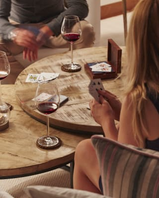 Close-up of a couple playing cards and drinking wine