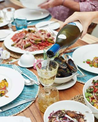 Une main verse du vin blanc dans un verre sur une table couverte de plats français