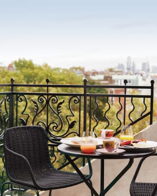 Wrought iron table set with breakfast on The Cadogan penthouse suite terrace, London skyline in the distance