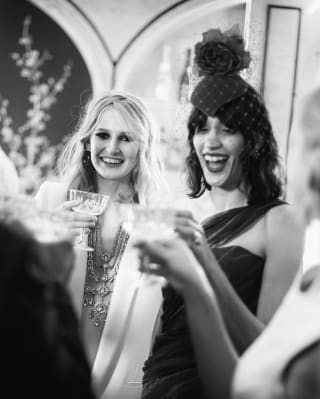 Two ladies smiling and raising champagne glasses