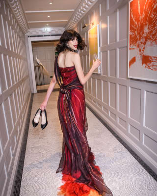 Lady in a red dress holding her heels and walking down a corridor