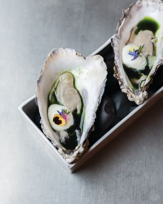 Close up of an oyster decorated with edible flowers