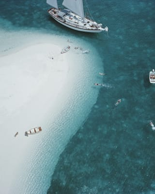 Aerial view of a sailing yacht beside a sand bank