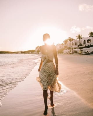Mulher com um vestido de verão andando descalça na praia ao pôr do sol