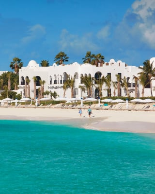 White domed hotel under blue skies next to crystal clear waters
