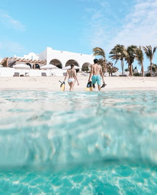 Couple with snorkels stepping out of crystal clear waters