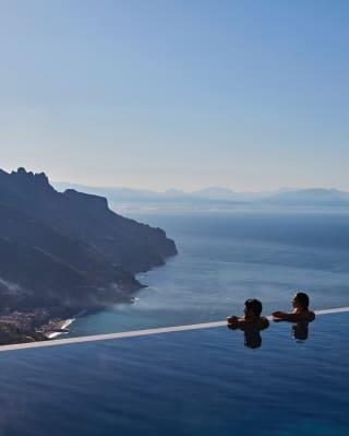 Au bord d'une piscine à débordement en plein air, un couple observe la côte amalfitaine
