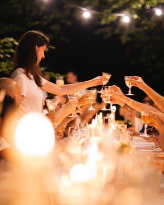 Una donna che si alza per un brindisi a una festa