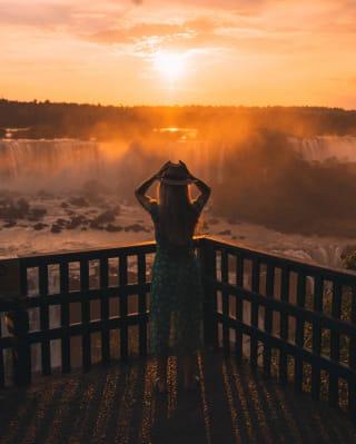 Lady using binoculars to watch the sunrise over Iguassu Falls