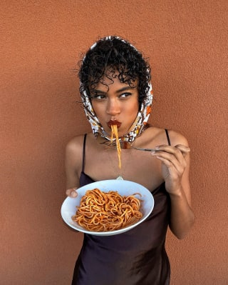Lady in a headscarf standing and eating spaghetti from a bowl