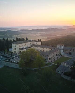 Aerial view of castello di casole with a sunset