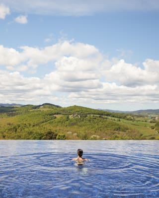 Lady in an infinity pool overlooking the Tuscan landscape