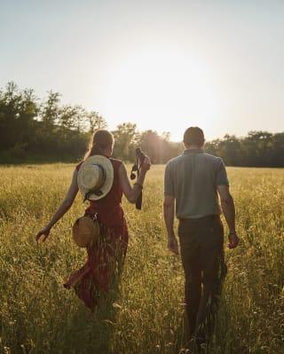 Man and woman with binoculars walking through tall grass