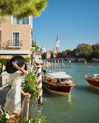 Lady in a black hat standing beside the Venice grand canal