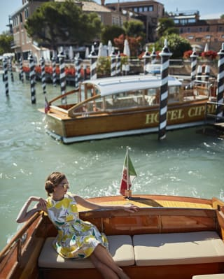 Lady in a yellow cocktail dress posing on Venetian water taxi