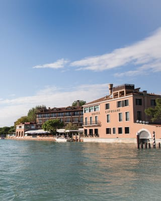 View from across the lagoon of Belmond Hotel Cipriani's coral-coloured exterior