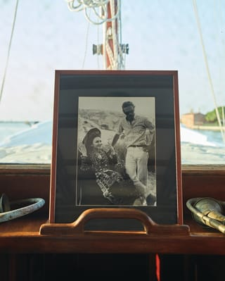 a black and white photo of a couple in a frame on a boat.