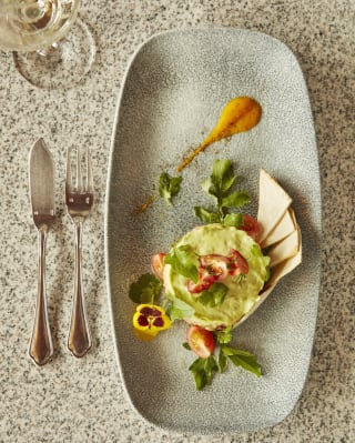 Birds-eye-view of a guacamole starter with melba toast on an oval plate