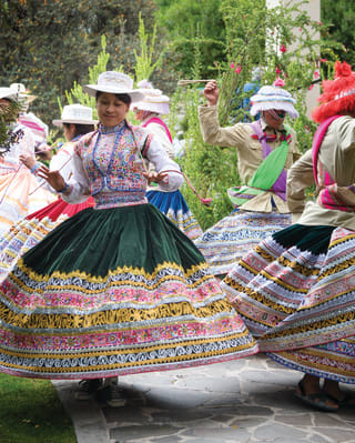 Ladies in traditional Peruvian dress whirling and dancing