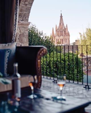 Vino rosé e bicchieri su un tavolino all'aperto con vista su San Miguel de Allende