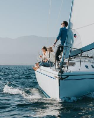 Amigos relaxando em um barco a vela no oceano Pacífico