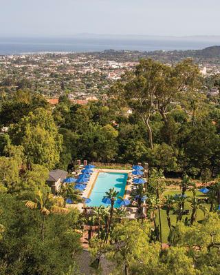 Vista aérea de una piscina de hotel al aire libre entre exuberantes árboles y vegetación