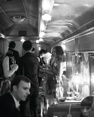 Guests mingling in a bustling bar car on a train
