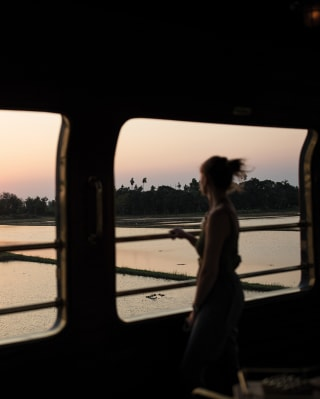 Lady gazing across the Thai countryside from an open-air train observation car