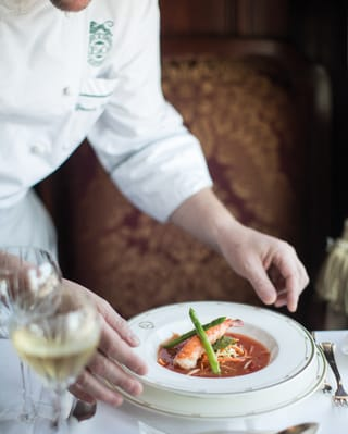 Chef carefully placing a soup dish at a linen-coated table