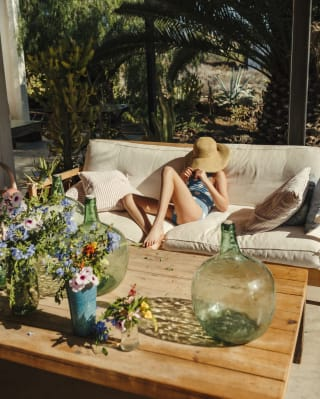Lady sitting on an outdoor sofa covering her face with a large sun hat