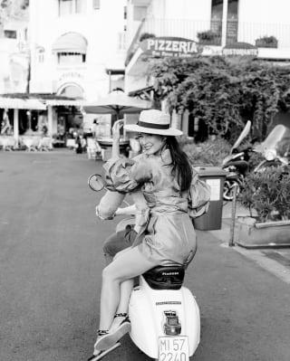 Lady on the back of a vespa in an Italian street