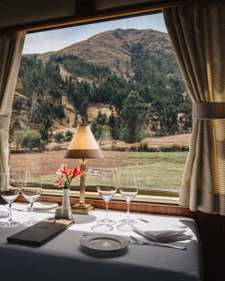 Formal dining table beside a picture window on a vintage train