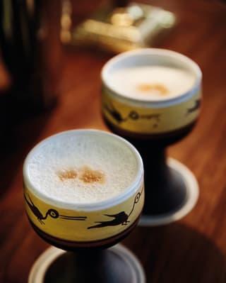 Dois coquetéis de pisco sour em xícaras de argila pintadas