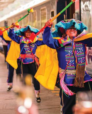 Man in colourful traditional Peruvian dress dancing alongside a train