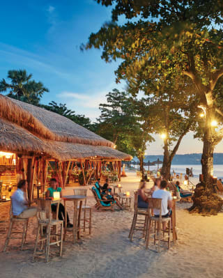 Guests relaxing at a beach bar at sunset