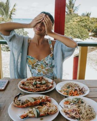 Mulher alegre cobrindo os olhos com as mãos em uma mesa cheia de pratos de frutos do mar